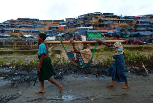 Deux enfants rohingya portent une vieille dame, près d'un camp de réfugiés à Cox's Bazar, au Bangladesh, le 13 septembre.