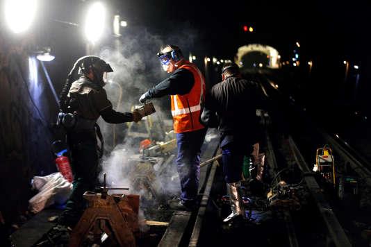 Des travailleurs de nuit pendant une opération de maintenance, dans le métro parisien, à la station Laumière, en juillet 2013.