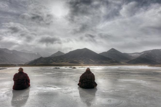 Deux moines tibétains sur une rivière gelée, devant la chaîne de l'Amnye Machen Shan, à Golok (Tibet oriental),au cœur de l'hiver, en 2016.