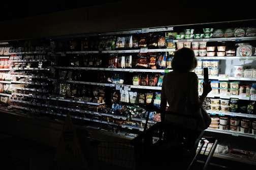 Des habitants de Naples, en Floride, font leurs courses à la lueur de leur téléphone portable dans un supermarché sans électricité, le 13 septembre.