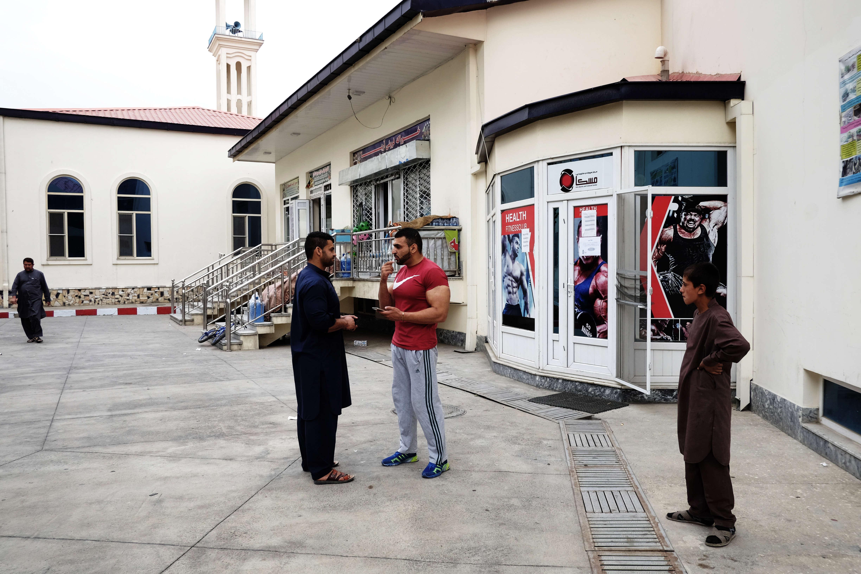 King, qui s'entraîne chez Gym Nation, discute avec le directeur d'une salle située dans un quartier huppé de Kaboul. Les bodybuildeurs sont souvent abordés par des curieux dans la rue. La pratique, exigeante, pousse de nombreux débutantsà tout arrêter quand les résultats tardent à apparaître.