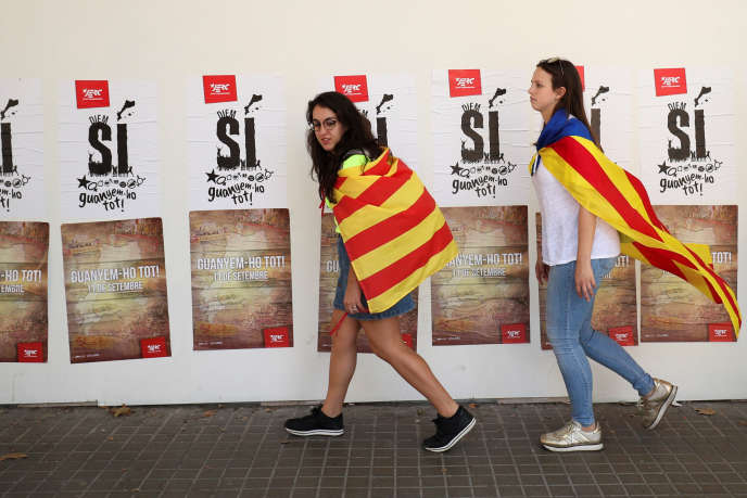 Des jeunes filles portant le drapeau catalan passent devant des affiches indépendantistes, à Barcelone le 11 septembre.