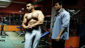 Osman, ancien M. Afghanistan, demande à son stagiaire, King, alors qu'il fléchit ses muscles et prend une pose à la Gym Nation où il forme les bodybuilders débutants.
