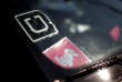 FILE PHOTO: A driver displays Uber and Lyft ride sharing signs in his car windscreen in Santa Monica, California, U.S., May 23, 2016. This logo has been updated and is no longer in use. REUTERS/Lucy Nicholson/File Photo