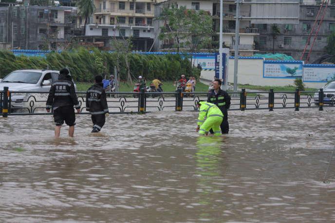 Les inondations ont fait un mort et les vents violents ont blessé trois personnes – ici des gens occupés à drainer l'eau d'une rue de Sanya, dans la province de Hainan, dans le sud de la Chine, après le passage du typhon Doksuri, le 15 septembre 2017.