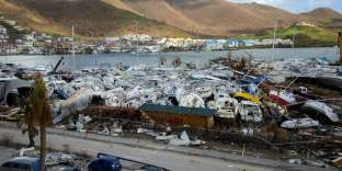 People walk past smashed boats on September 16, 2017 at Marigot shipyard on the French Caribbean island of Saint Martin after the island was hit by Hurricane Irma. The Caribbean island of St Martin was a place of spectacular inequalities before Hurricane Irma flattened rich and poor neighbourhoods alike -- but some residents now dream of a fresh start. Ten days after the storm devastated the island, cleaning up and reconstruction remain a priority for St Martin, although repairing roads and buildings before the high season, which usually starts in November and runs until April, seems nearly impossible. / AFP / Helene Valenzuela