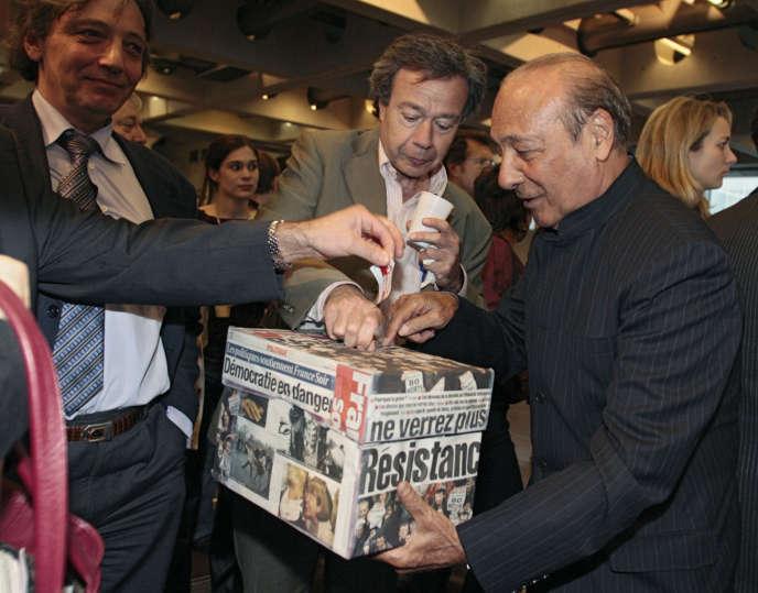 L'éditorialiste Paul Wermus, au centre, et le publicitaire Jacques Seguela, à droite,déposent de l'argent dans une boîte de soutien au quotidien «France Soir», le 25avril 2006 à l'arche de La Défense à Paris.