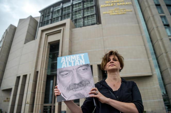 Une journaliste pose avec le portrait du journaliste turc Ahmet Altan le 19 juin devant le palais de justice d'Istanbul.