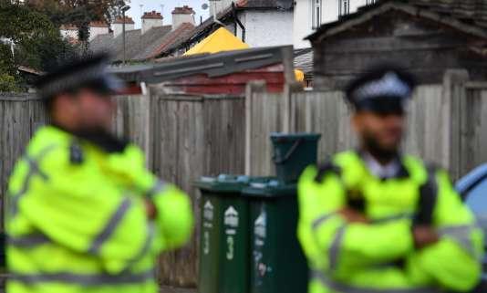Des officiers de police devant un cordon de sécurité aux abords de la maison du couple Jones, àSunbury-on-Thames, (Surrey), à 25kilomètres au sud-ouest de Londres,le 18 septembre.