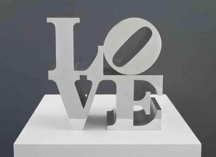 """«Dans cette œuvre de Robert Indiana, le mot """"LOVE"""" est utilisé comme sujet de sa sculpture. Reprise sous plusieurs formes, l'imagerie """"LOVE"""" de cet artiste est devenue un véritable symbole de la culture populaire des années 1960, résonnant politiquement à travers la société américaine.»"""