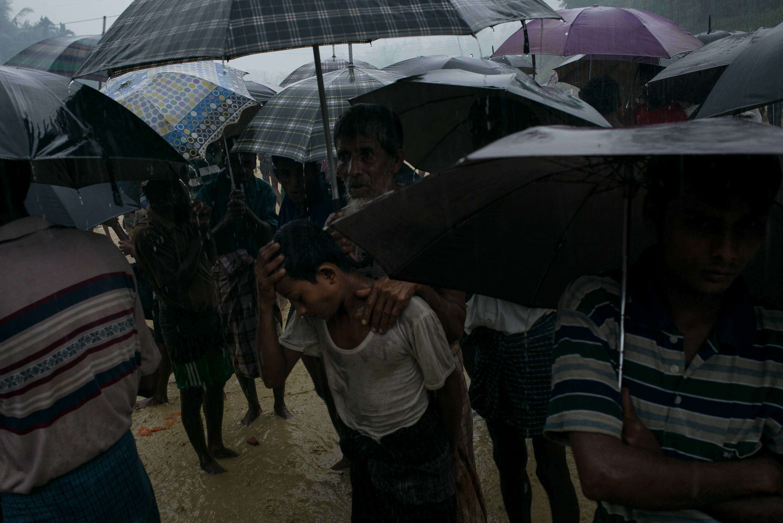 Un père et son fils, épuisés, pendant une distribution de provisions près de la route. Les Rohingyaattendent sous la pluie, dans la boue, parfois pendant plusieurs heures.