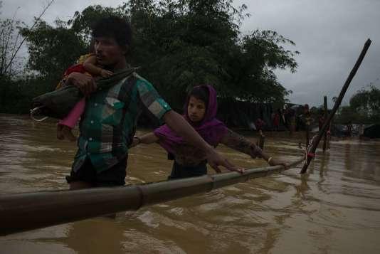 Un homme, sa femme et sa fille quittent une zone inondée pour accèder aux collines, sur la route entre Teknaf et Balukhali, le 19 septembre.