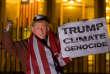 Un homme portant un masque de Donald Trump, brandit une pancarte «Trump, climat, génocide»le 18novembre à Londres.
