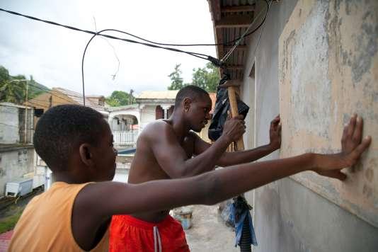 Deux jeunes hommes accrochent des planches en bois sur les fenêtres à Trois-Rivières en Guadeloupe.