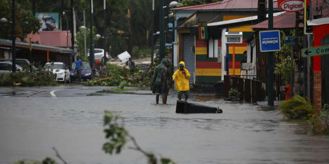 People walk in a flooded street after the passage of Hurricane Maria in Pointe-a-Pitre, Guadeloupe island, France, September 19, 2017. REUTERS/Andres Martinez Casares