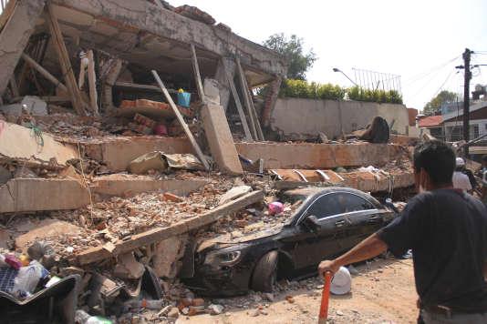 Une voiture écrasée devant les ruines du collège Enrique-Rebsamen où des dizaines d'enfants sont portés disparus, à Mexico, le 19 septembre.