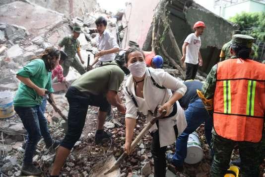 Sauveteurs et volontaires fouillent les décombres d'un immeuble effondré à la recherche de survivants, à Mexico, le 19septembre.