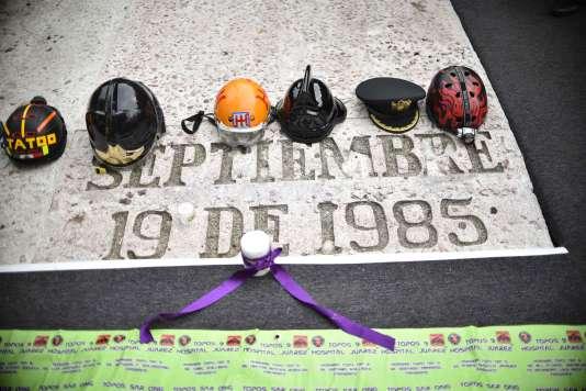 Des casques de sauveteurs, pompiers et policiers sont disposés sur une plaque commémorant le tremblement de terre du 19septembre 1985, lors d'une cérémonie anniversaire à Mexico, le 19septembre.