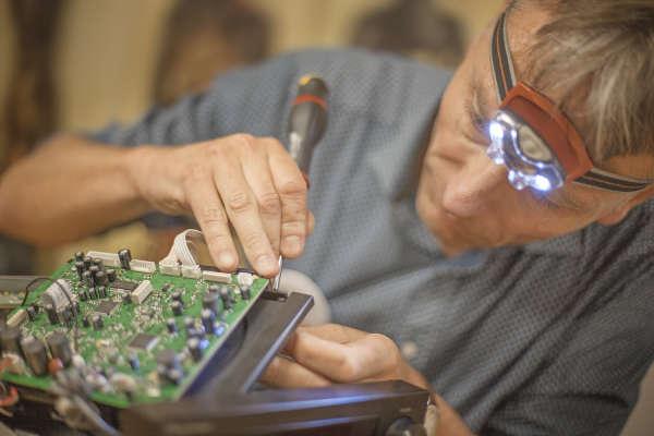 Emmanuel répare la chaîne hi-fi apportée par Carolina.