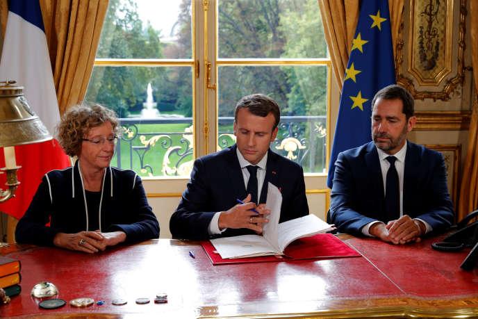 Emmanuel Macron, entouré de Muriel Pénicaud et Christophe Castaner, signe les ordonnances réformant le code du travail, à l'Elysée, le 22 septembre.