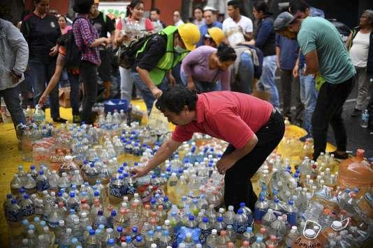Des volontaires recueillent des bouteilles d'eau, à Mexico, le 21 septembre.