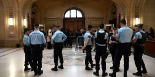 French gendarmes look on as members of the public line up for security checks as they arrive at The Paris Courthouse in Paris on September 22, 2017, for the start of the trial of nine defendants over an attack that turned a police car with officers onboard into a fireball. Nine people are facing trial over a May 18, 2016, attack by demonstrators that turned a police car with officers onboard into a fireball, during an unauthorized counter-demonstration against police violence in Paris. / AFP / Lionel BONAVENTURE