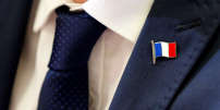A French flag is pictured on a jacket of security member as Member of parliament Marine Le Pen of France's far-right National Front (FN) political party speaks with journalists during a news conference in Toulouse, France September 23, 2017.  REUTERS/Regis Duvignau