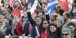 La France Insoumise (LFI) leftist party parliamentary group President Jean-Luc Melenchon (C), flanked by party's spokeperson Raquel Garrido (2R), waves during a protest over the government's labour reforms in Paris on September 23, 2017. The third in a series of nationwide protests comes a day after French President signed his signature reforms into law using a fast-tracked procedure that avoided a lengthy parliamentary debate. / AFP / GEOFFROY VAN DER HASSELT