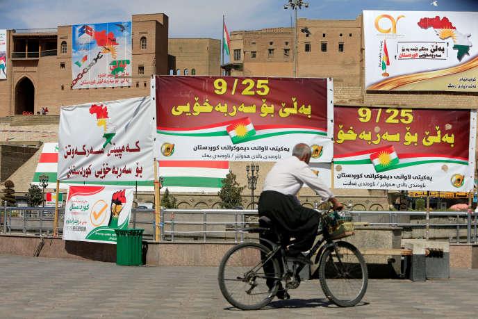 Un homme passe devant des bannières en faveur du référendum, le 24 septembre à Erbil, capitale de la région autonome du Kurdistan.