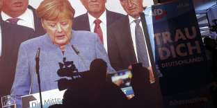 """Christian Democratic Union (CDU) party leader and German Chancellor Angela Merkelis is seen on a screen next to banners of the anti-immigration party Alternative fuer Deutschland (AfD) that read """"I dare you Germany!"""" at AfD election party after first exit polls in the German general election (Bundestagswahl) in Berlin, Germany, September 24, 2017. REUTERS/Wolfgang Rattay"""