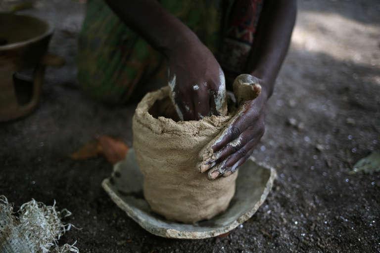 Sur l'île d'Idjiwi, une femme pygmée fabrique bois et marmite en argile qui seront vendus au marché pour quelques francs congolais. CREDITS : THERESE DI CAMPO|REUTERS