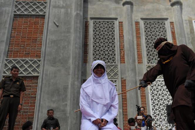 Une jeune femme reçoit des coups de canne en rotin sur le parvis d'une mosquée de Banda Aceh, le 1er août 2016.