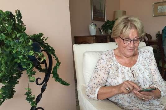 Claudine, 78ans, consulte son smartphone dans son appartement, à Nice, le 26septembre.