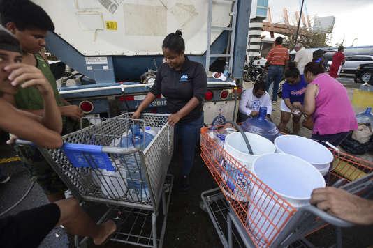 Des employés municipaux remplissent des bidons d'eau potable à Porto Rico.