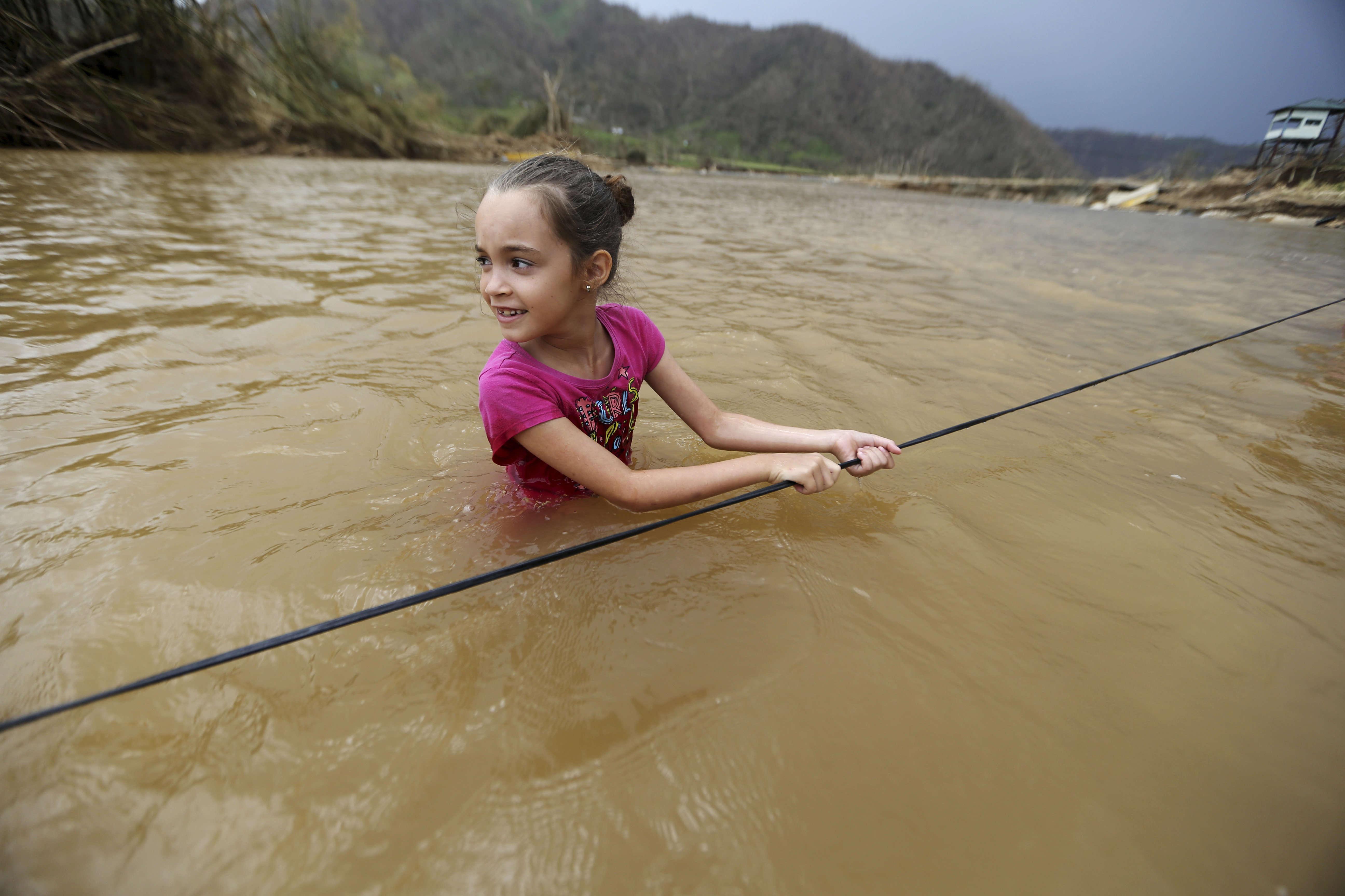 Ruby Rodriguez, 8ans, regarde sa mère alors qu'elle traverse la rivière SanLorenzo (municipalité de Morovis). Le pont a été balayé par l'ouragan Maria.