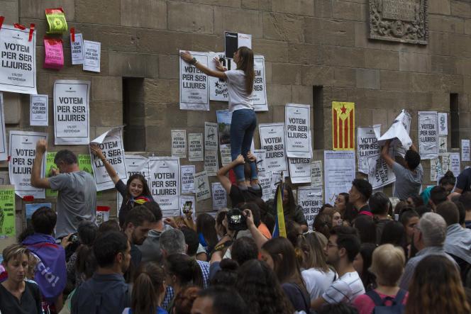 Des partisans du référendum d'autodétermination défient l'interdiction de faire campagne en collant des affiches, à Lleida, le 21 septembre.