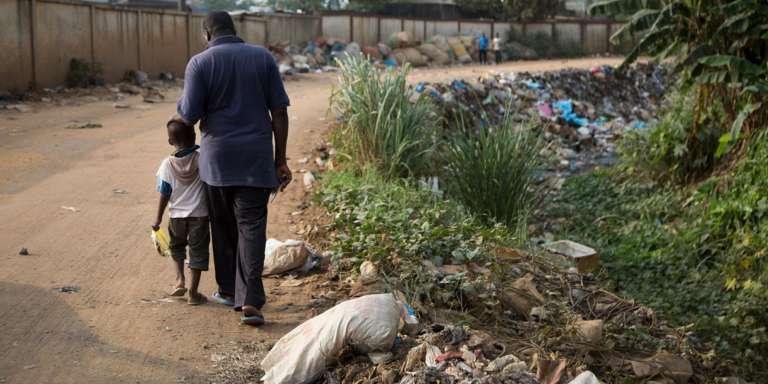 Moustapha Sangaré, ancien travailleur à la décharge d'Akouédo, et son fils, au bord du caniveau où a été déversée une partie des déchets toxiques du « Probo-Koala » en 2006.