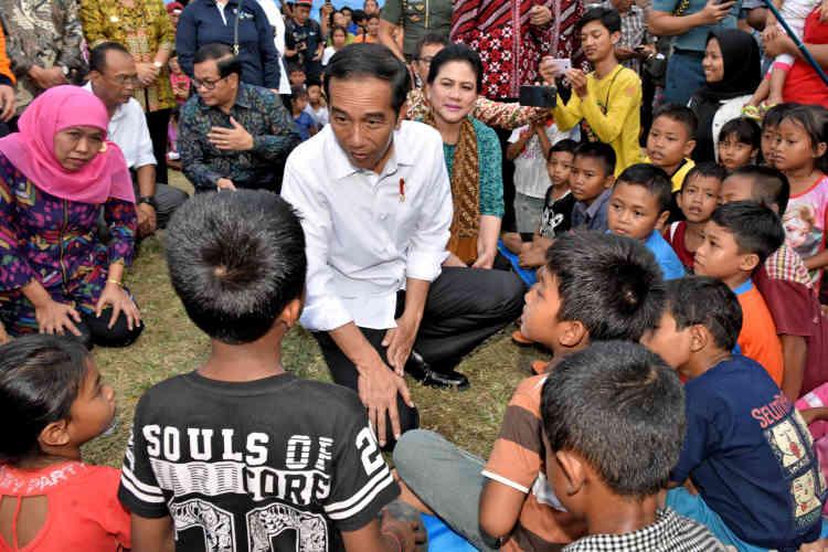 Le président indonésien, Joko Widodo, parle avec des enfants du camp de Karangasem.