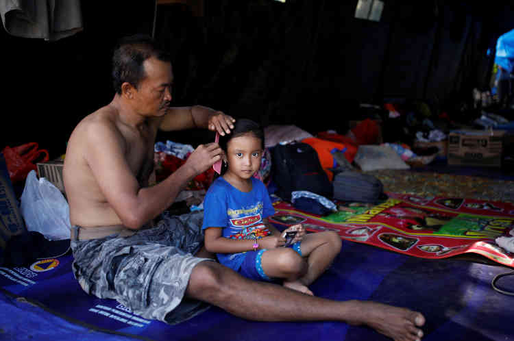 Un homme peigne les cheveux de sa fille dans une tente dans un centre d'évacuation temporaire, à Manggis, sur l'île de Bali.Le nombre d'habitants évacués ces derniers jours continue d'augmenter. Il est passé de 122490 jeudi à 144389 vendredi, selon des responsables locaux.