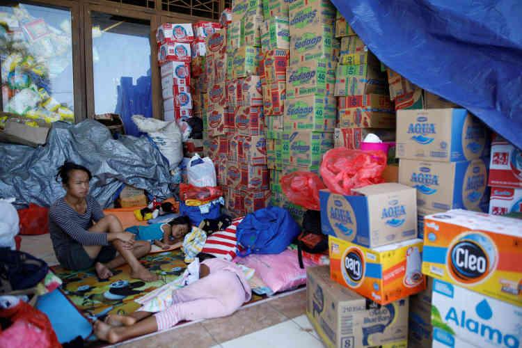 Des enfants se reposent à côté d'un stock de dons à l'extérieur d'un centre d'évacuation temporaire à Klungkung.Les déplacés sont accueillis dans près de 500centres d'hébergement dispersés dans neuf districts, et certains ont traversé le détroit de Lombok pour être accueillis sur l'île voisine du même nom.
