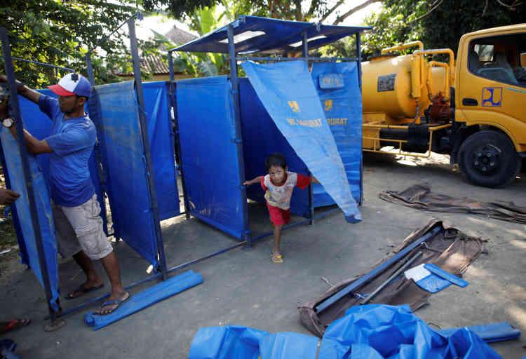 Un garçon joue dans les douches mobiles du camps à Manggis.