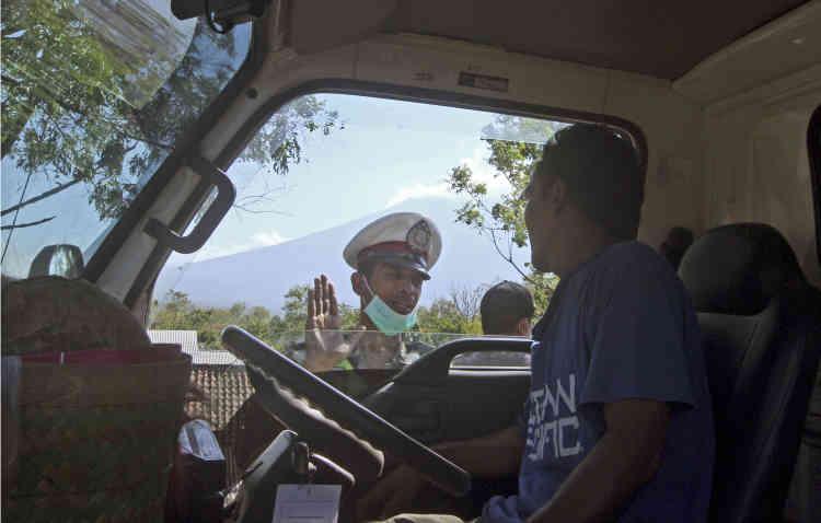 Un policier met en garde un chauffeur de camion qui se dirige vers la zone dangereuse.Les autorités recommandent de rester à plus de neuf kilomètres du cratère du volcan, loin des zones touristiques.