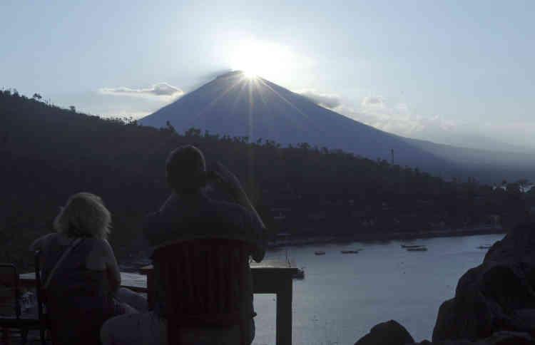 A Karangasem, des touristes étrangers regardent le coucher de soleil sur le volcan Agung.