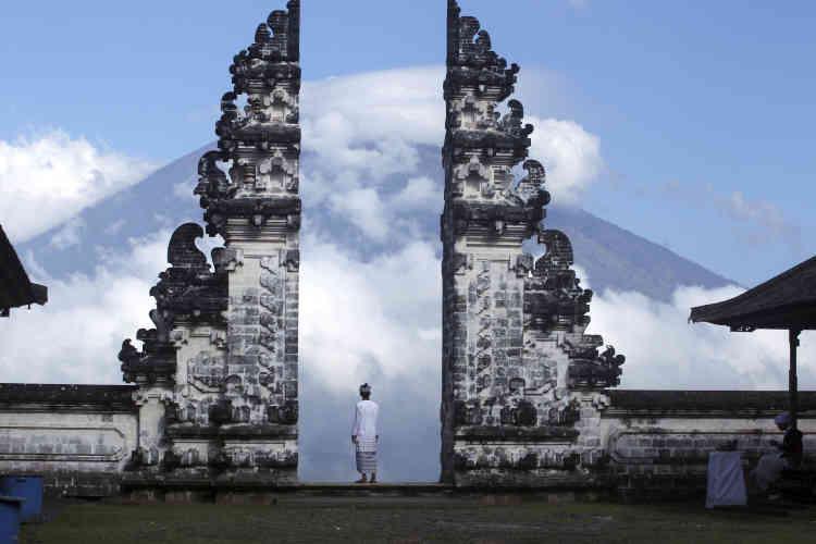 Un Balinais regarde le volcan Agung, couvert de nuages, depuis un temple de Karangasem. Des nuages contenant des vapeurs d'acide sulfurique ont été observés à une altitude allant de 50 à 200 mètres du sommet, d'après les relevéssatellitaires.