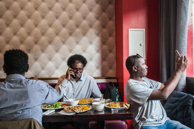 A la table du restaurant érythréen Le Saint-Jean, dans le 18e arrondissement de Paris, Boklyn, Issam et Abdo Rsol, qui ne résiste pas à faire un selfie avec les plats érythréens et soudanais qui viennent d'être servis.