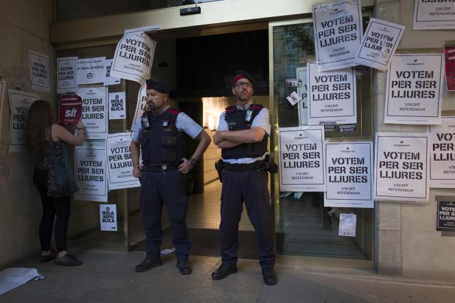 A Lleida,en Catalogne, des militants indépendantistes collent, devant des membres de la police catalanes, des affiches interdites appelant à voter au référendum du 1er octobre.