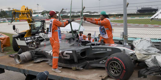 Evacuation de la voiture du pilote Haas Romain Grosjean, après sa violente sortie de route au 14e tour, lors des essais à Sepang (Malaisie), le 29 septembre.