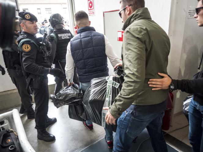 Les forces de l'ordre emmènent une urne et des bulletins, dans le gymnase où était installé le bureau de vote de Sant Julia de Ramis, dans la province de Gérone, le 1er octobre.