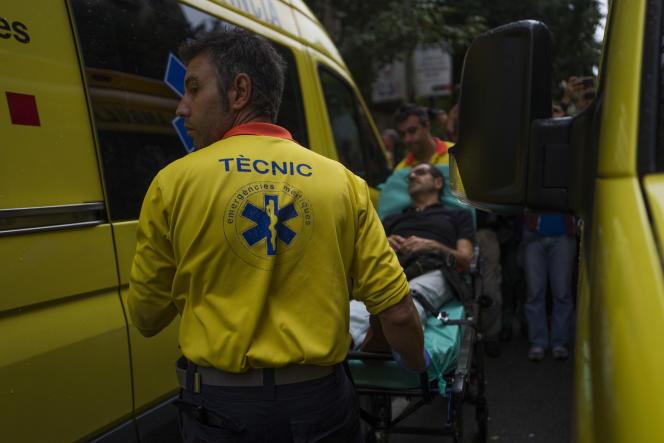 Les secours emmènent un blessé après une altercation entre électeurs et forces de l'ordre, au bureau de vote Ramon-Lull près de la Sagrada Familia à Barcelone, le 1er octobre.