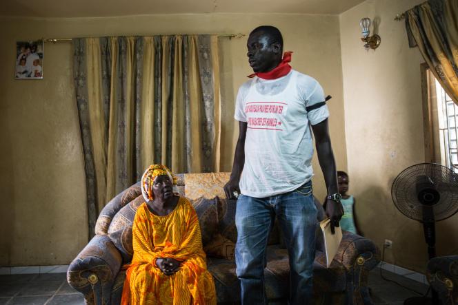 Macodou Fall discute avec sa tante dans la maison familiale de Thiaroye, quartier de Dakar, avant de mener le Collectif des personnes affectées par le projet TER manifester le 30 septembre 2017 contre des indemnisations d'expropriation jugéestrop faibles.